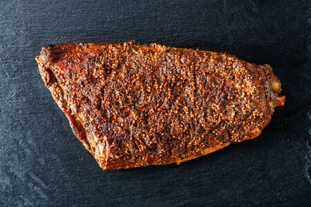 Oven Baked spicy Barbecue whole Pork Brisket on a black slate tray, close-up, flat lay, macro Stock Photo