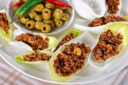 close-up of Endive Boats with ground beef and chopped green olives fillings served on a white plate with sour cream, olives, chili peppers, horizontal view from above, macro Archivio Fotografico