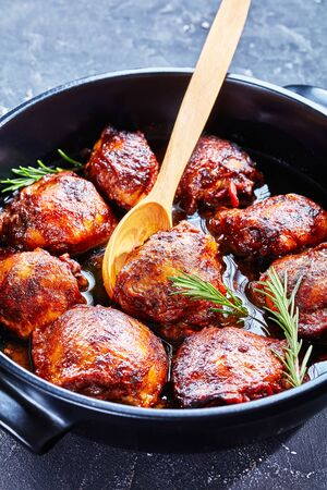 close-up of tender and juicy Brown Sugar Mustard Chicken thighs with a wooden spoon in a dutch oven on a concrete table, vertical view from above Standard-Bild