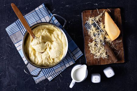 aligot, cheesy mashed potato dish in a metal pot with wooden spoon on a concrete kitchen table, with ingredients, french cuisine, horizontal view from above, flat lay
