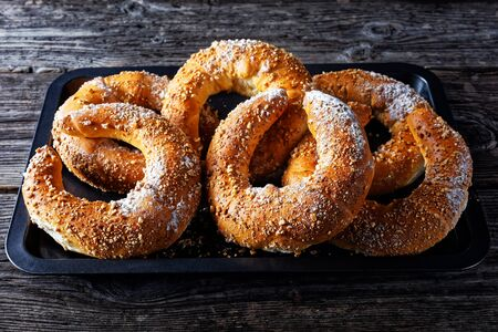 Austrian pastry rolls kifli of kipfel sprinkled with nuts and icing sugar, served on an old barn wooden background, close-up