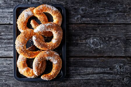 Austrian dessert kifli of kipfel crescent-shaped sweet pastry sprinkled with nuts and icing sugar, served on a old barn wooden background, top view, copy space