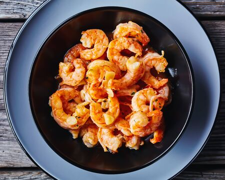 Shrimp scampi with garlic and butter sauce sprinkled with parsley served on a black plate on rustic old wooden background   horizontal orientation, top view, close-up
