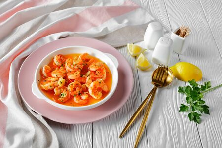 Prawn scampi with garlic and butter sauce sprinkled with parsley, served with lemon wedges with salt and pepper on a pink plate on white wooden background, horizontal orientation, close-up