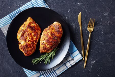 Two chicken breasts roasted in spices served on a black plate on a dark concrete background with golden cutlery with a napkin, top view, horizontal orientation