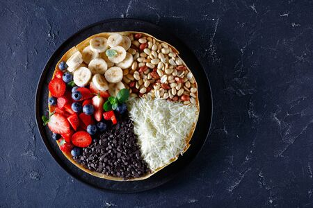 Thick indonesian pancake with sweet filling: chocolate chips, peanuts, strawberries, blueberries, banana, cheese, with mint on top on a dark concrete background, view from above, close-up