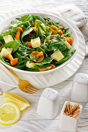 close-up of arugula, spinach, honey mushrooms, and cubed cheddar cheese salad in a white bowl. lemon slices, golden fork on a wooden table, vertical view from above Stok Fotoğraf
