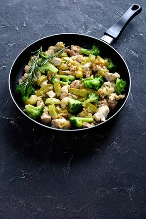 Fitness menu: fried chicken meat with green vegetables: zucchini, broccoli, onion, and rosemary on a skillet on a dark concrete background, close-up, vertical orientation, copy space 写真素材