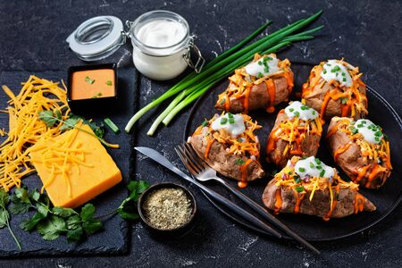 Paleo diet: loaded sweet potato with baked chicken breast with ranch seasoning, paprika sauce, smoked cheddar, and sour cream on top, cilantro on a dark concrete background, close-up, horizontal