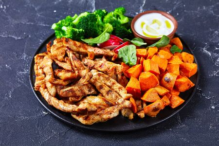 Easy recipe: chicken breast and vegetables of baked sweet potato,  boiled broccoli on a black plate on a dark concrete background with sour cream, radish, and spinach, close-up