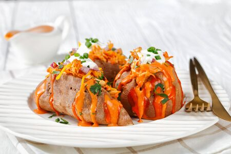 Sweet potato loaded with shredded chicken fillet, smoked cheddar cheese, cilantro, scallion, sour cream on top on a white wooden background on a white plate, horizontal view, close-up