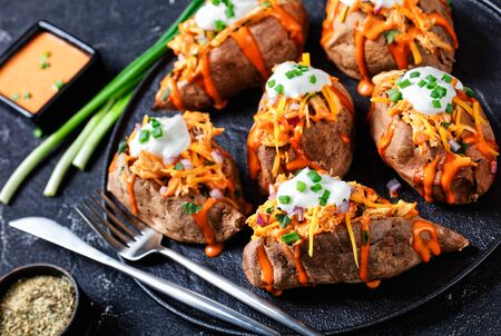 Spicy buffalo loaded sweet potato stuffed with chicken breast  smoked cheddar, cilantro, and red onion, sour cream on top on a dark concrete background, close-up