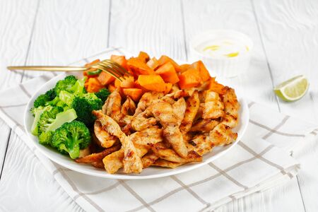 Low-fat chicken breast and veggies with sweet potato and boiled broccoli on a white plate on a white wooden background with sour cream and a lime wedge, top view, horizontal orientation, close-up 版權商用圖片