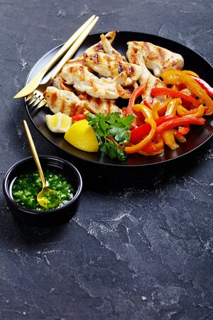 Skinny dish of sweet peppers with grilled chicken steaks fresh parsley lemon, on top on a black plate on a dark concrete background, vertical orientation, close-up Archivio Fotografico