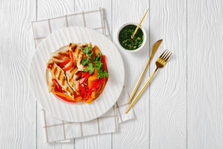 Easy low-fat dish of sauteed bell peppers with grilled chicken strips fresh parsley on top and green herb sauce on a white plate with golden cutlery on a wooden table, top view, copy space