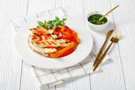 Grilled chicken steaks with stir fry sweet pepper strips, fresh parsley on top and green herb sauce on a white plate on a white wooden background, close-up