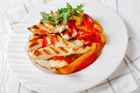 Close-up on a white plate with weight loss meal of grilled chicken steaks with stir fry sweet pepper strips, fresh parsley on top and green herb sauce on a white plate on a wooden background
