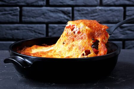 Cannelloni pasta stuffed with beef bolognese sauce and baked with passata and mozzarella cheese on top served on a black baking dish on dark concrete background in front of black brick wall Stock Photo