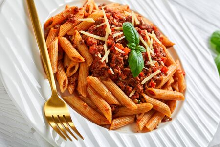 close-up of pasta bolognese topped with shredded parmesan and basil on a white plate, on a wooden table, horizontal view from above