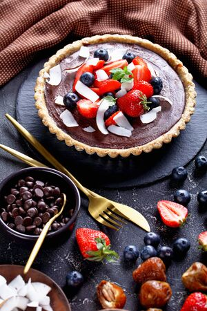 Easy chocolate tart decorated with fresh strawberries, blueberries, coconut chips on top, served on a dark concrete background with ingredients: dates, rolled oats, chocolate chips, close-up