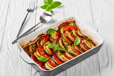 close-up of french tian provencal, baked sliced layered vegetables in a baking dish on a white wooden table with basil and silver cutlery, horizontal view from above