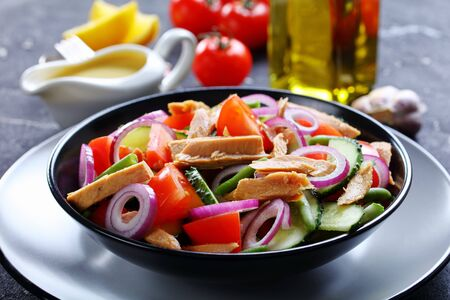 Easy tuna and green bean salad with vegetables: tomatoes, cucumber, red onion on a dark concrete background with olive oil, garlic and lemon dressing