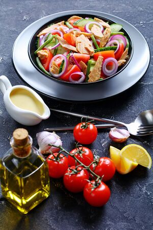 Refreshing vitamin green bean and tuna salad with vegetables: tomatoes, cucumber, red onion on a dark concrete background with olive oil, garlic and lemon dressing