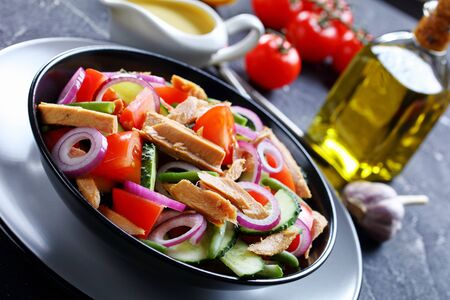 Close-up on a black plate of canned tuna and green bean salad with lemon dressing and vegetables: tomatoes, cucumber, red onion on a dark concrete background with olive oil