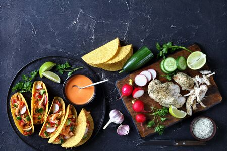 Buffalo Chicken Corn Taco shells loaded with fresh greens and vegetables on a black plate with lime and buffalo sauce with ingredients on a concrete table, flat lay, free space