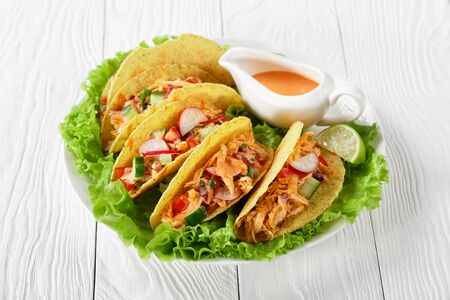 corn Taco shells loaded with shredded chicken breast, fresh greens and vegetables with lime and buffalo sauce on a white plate on a wooden table, horizontal view from above