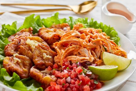 Latin american takeout food fried green plantains tossed with garlic served with shredded chicken with buffalo sauce, and pico de gallo with lime on a white plate, on a white wooden table, close-up