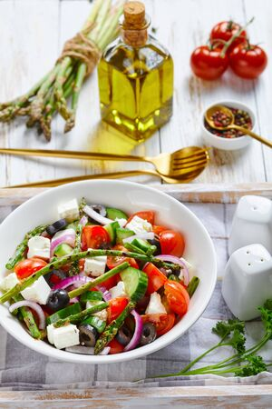 Classic spring asparagus salad with feta cheese, tomatoes, cucumbers, black olives, red onion, served on a white bowl on a serving tray with a bunch of asparagus spears, olive oil, parsley, close-up