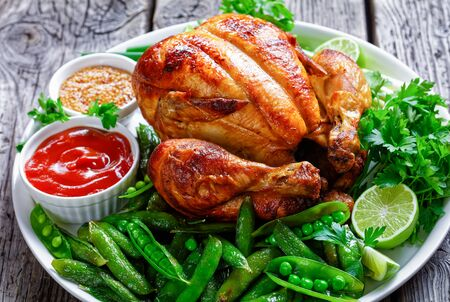 close-up of a whole roast chicken served with fried pods of green peas, fresh green onion, parsley, lime, tomato sauce and whole grain mustard on a white plate on a dark wooden table, landscape view