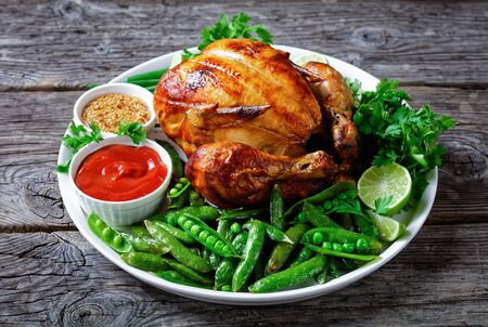 rotisserie chicken served with fried pods of green peas, fresh green onion, parsley, lime, tomato sauce and mustard on a white plate on a rustic wooden table, landscape view