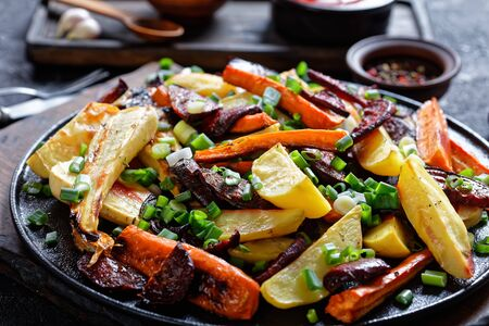 Close-up of grilled sliced beetroot, potato wedges, parsnips, carrots sprinkled with chopped green onion on a wooden board Stock Photo