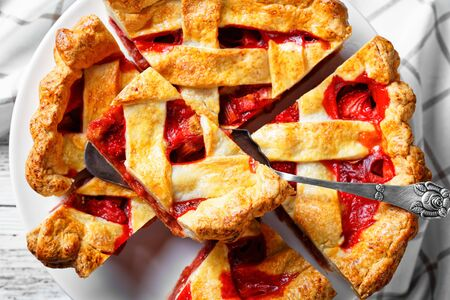 close-up of freshly baked Homemade Strawberry Rhubarb Pie slices on a white cake plate on a wooden table, flat lay, Zdjęcie Seryjne