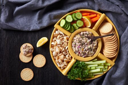 Tuna capers pickles Spread set served with carrots and celery sticks, sliced fresh cucumber, crackers and pork rinds in bowls on a dark wooden table, Philippines cuisine, flat lay, free space Banque d'images