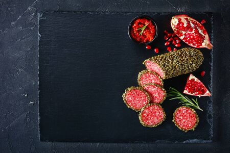 salami coated with whole green peppercorns and have sliced on a black stone board and served with pomegranate and salsa, flat lay, close-up, horizontal view from above