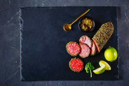 salami coated with whole green peppercorns and have sliced on a black stone board and served with basil pesto and  lime wedges, flat lay, close-up, horizontal view from above