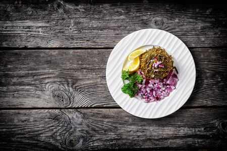 Seaweed salad, of marinated wakame seaweed with oil, red onion and lemon wedges, served on a white  plate with parsley on a wooden background, top view, copy space