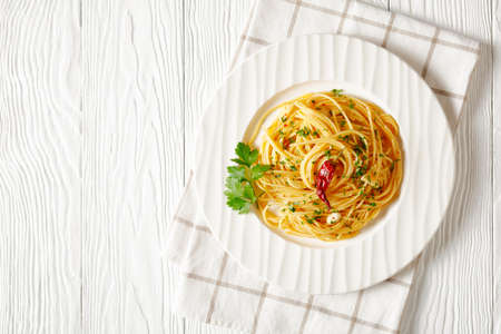 Spaghetti Alla colatura di alici, Spaghetti with anchovy sauce, pimento pepper, garlic and parsley on a white plate on a white wooden table, horizontal view from above, flat lay, free space