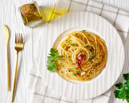 Spaghetti Alla colatura di alici, Spaghetti with anchovy sauce, pimento pepper, garlic and parsley on a white plate on a white wooden table, horizontal view from above, flat lay