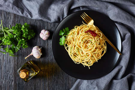 pasta Alla colatura di alici, Spaghetti with anchovy sauce, pimento pepper, garlic and parsley on a black plate with golden fork on a dark wooden table, top view, flat lay