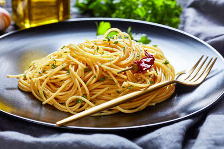 Spaghetti Alla colatura di alici, Spaghetti tossed with anchovy sauce, pimento pepper, garlic and parsley on a black plate with golden fork on a dark wooden table, landscape view, close-up