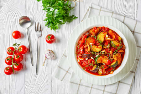 vegetable stew, eggplant, onion, zucchini with tomato sauce, garlic and herbs in a white bowl on a wooden table, landscape view from above, flat lay, free space