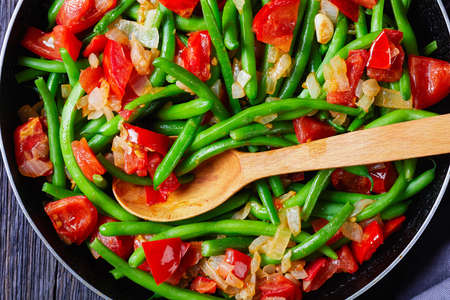 close-up of Caribbean stir-fry green beans with onions and tomatoes, Fry bodi in a skillet on a wooden table, flat lay, horizontal view from above, macro