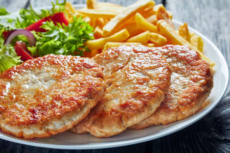 close-up of freshly fried three turkey burgers served with lettuce tomato salad and french fries on a white plate on a rustic wooden table, horizontal view from above, macro