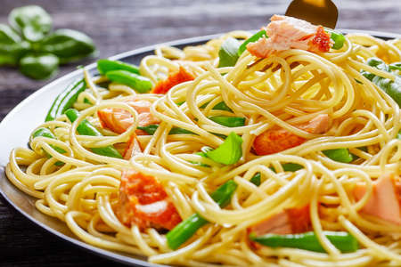 Close-up of the fork with italian spaghetti, green bean, and salmon with fresh basil on top served on a black plate on a dark wooden background Standard-Bild