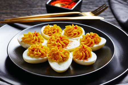 Simple deviled eggs of smashed egg yolks mustard, mayonnaise, white vinegar sprinkled with smoked paprika on a black plate on a dark wooden background, golden cutlery, close-up 免版税图像