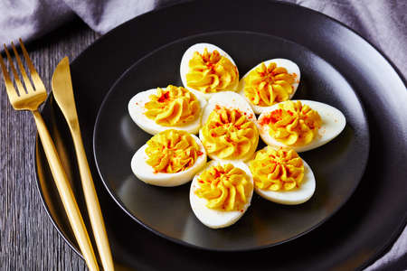 Homemade deviled eggs filled with smashed egg yolks mustard, mayonnaise, white vinegar sprinkled with smoked paprika on a black plate with cutlery on a dark wooden background, close-up